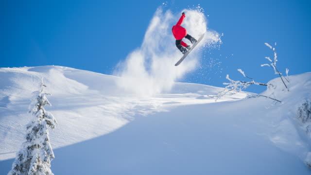 snowboarder performing a stunt on sunny winter day - сноубординг стоковые видео и кадры b-roll