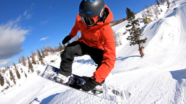 snowboarder performing a trick, jumping and turning mid-air in a snowpark - snowboarding video stock e b–roll