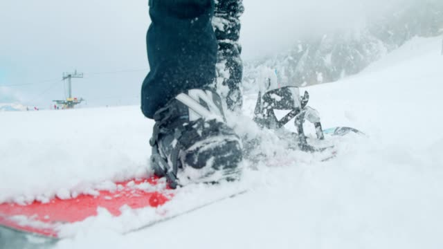 vídeos de stock e filmes b-roll de slo mo snowboarder preparing for winter adventure - bota