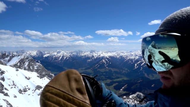 rallent snowboarder mette su i suoi occhiali da sci - sci freestyle video stock e b–roll