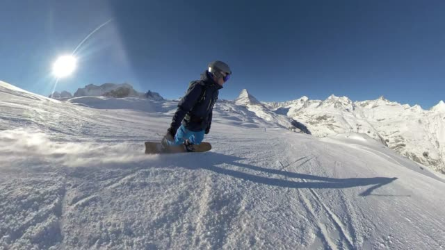 snowboarder riding down a hill with the matterhorn - fish eye video stock e b–roll