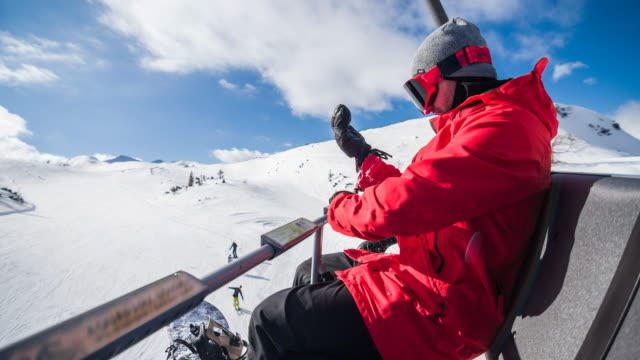 snowboarder riding on chairlift, readjusting his gloves - guanto indumento sportivo protettivo video stock e b–roll