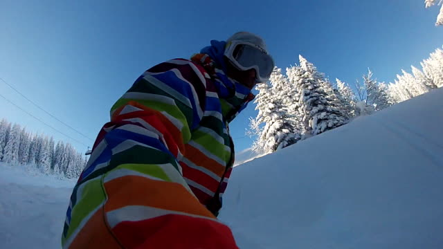 Snowboarder riding powder on a sunny winter day video