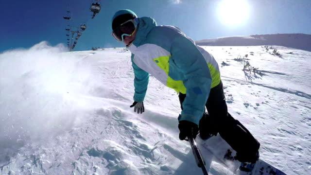 SELFIE: Snowboarder riding powder snow in mountain ski resort video