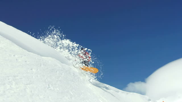 Snowboarder sends snow flying into air, super slow motion video