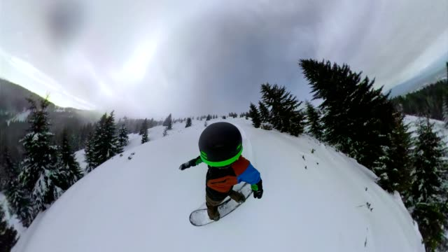 Snowboarder shredding  fresh powder snow on a descent Young skilled snowboarder enjoys staying and riding in a ski resort on a cold sunny day crash helmet stock videos & royalty-free footage