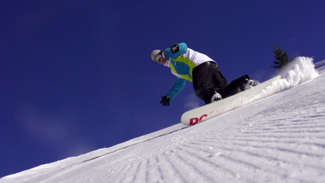 SLOW MOTION: Snowboarder spraying snow into the camera video