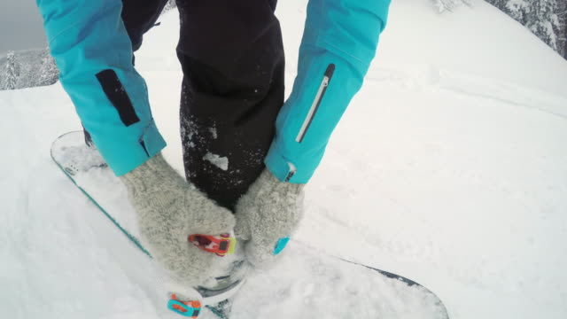 POV Snowboarder strapping into bindings video