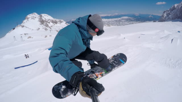 Snowboarder taking a selfie while jumping over kicker video
