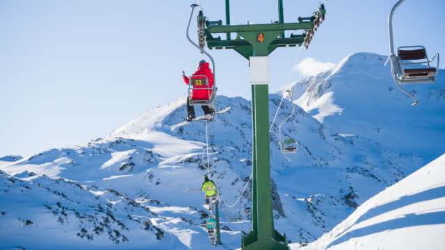 Snowboarder taking pictures with smartphone while riding a ski lift to the top of the snowcapped mountain