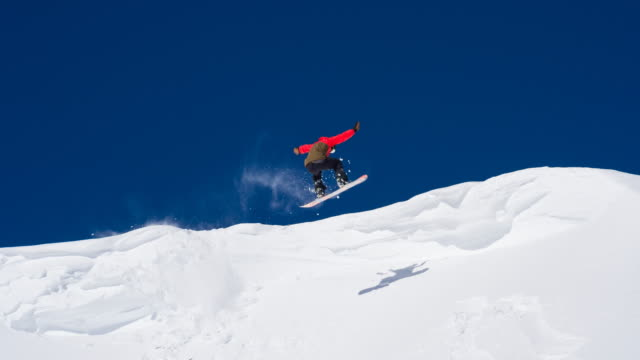 snowboarder unsuccessfully performing a stunt, falling - snowboarding video stock e b–roll