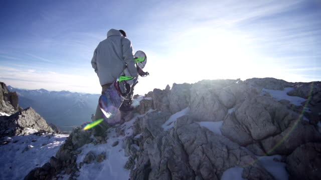 Snowboarder walking up a rocky mountain video