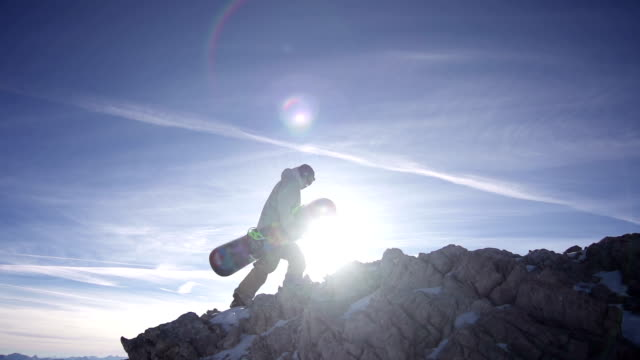 Snowboarder walking up the mountain video