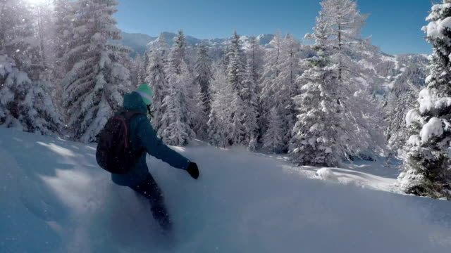CLOSE UP: Snowboarder woman riding fresh powder snow in snowy mountains video