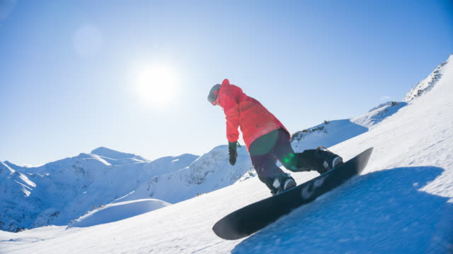 snowboarding on a snowcapped mountain on a beautiful sunny day - snowboarding video stock e b–roll