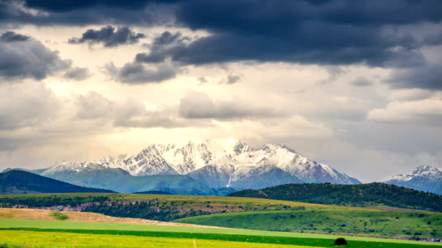 Snow-capped mountain top against a backdrop of thunderclouds and wheat fields in summer. 4K TimeLaps Snow-capped mountain top against a backdrop of thunderclouds and wheat fields in summer. 4K TimeLaps. kazakhstan stock videos & royalty-free footage