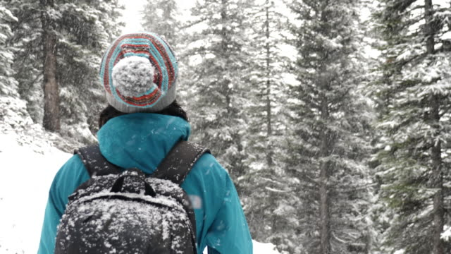 Snowflakes falling on Hiking woman's hands