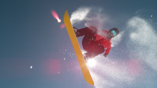 SLOW MOTION: Snowflakes shining in winter sun as snowboarder jumps over camera