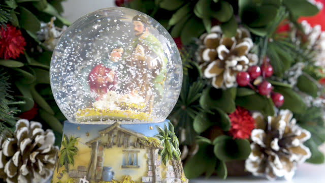 Snowglobe with child in the manger on Christmas background. Flat plane