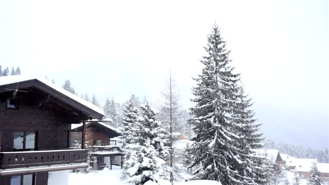 Snowing in the winter ski resort Snow falling over winter holiday chalets in the snowy Austrian Alps mountains seen from the snow covered balcony of a chalet. chalet stock videos & royalty-free footage