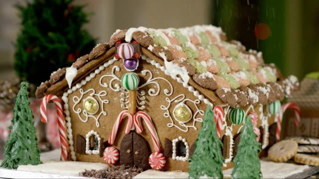 schneien auf einem lebkuchenhaus - lebkuchenhaus stock-videos und b-roll-filmmaterial
