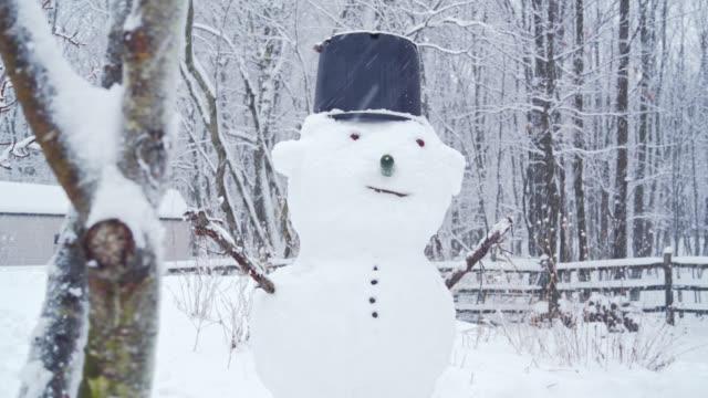 vídeos y material grabado en eventos de stock de muñeco de nieve en el patio bajo la nieve en, un día el invierno - snowman