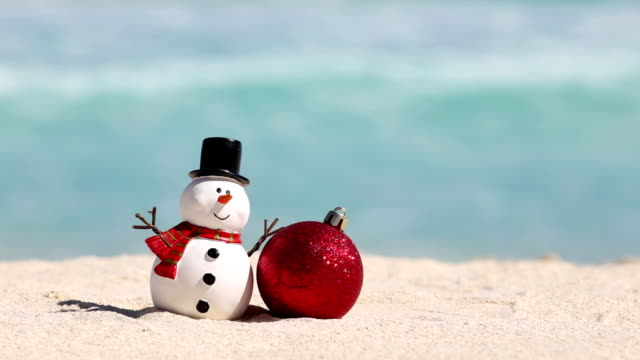 Snowman toy and christmas decoration ball at sandy beach on Caribbean sea background Snowman toy and christmas decoration ball at sandy beach on Caribbean sea background. New Year celebration snowman stock videos & royalty-free footage