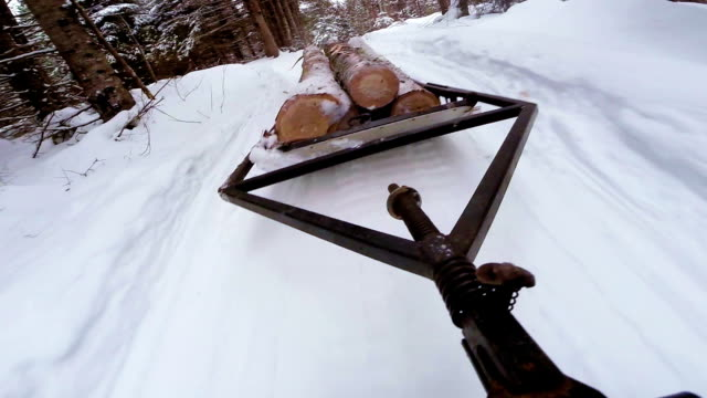 Snowmobile Dragging trunk of Timber on a Sled video