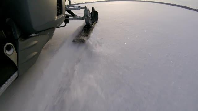 Snowmobile rides on a frozen lake. video