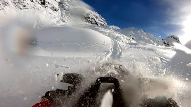 Snowmobiling fresh powder in the mountains