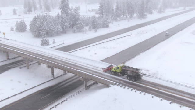 aerial: snowplow cleans the highway overpass during a snowstorm in washington - соль минерал стоковые видео и кадры b-roll