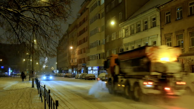 Snowplow rides on a snow covered street, Central Europe, Night video