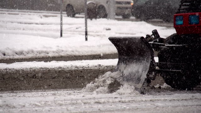 Snowplows on the Road Snowplows removes snow from city streets during snowfall. Slow Motion at a rate of 240 fps plow stock videos & royalty-free footage