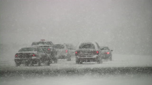 Snowstorm. Winter traffic. Cars on slippery road. Snowfall, snowflakes. video