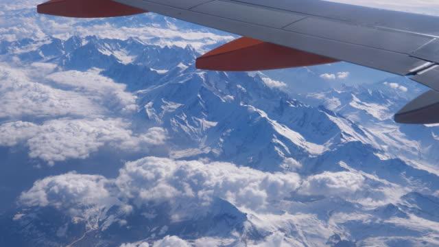 Bидео Snowy Alps mountain range under airplane wing