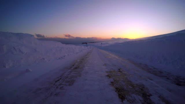 Snowy winter road drive at dusk- 4K - video