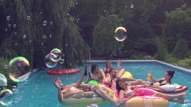 vídeos de stock e filmes b-roll de soap bubbles young adult pool party outdoor summer bbq - brinquedos na piscina