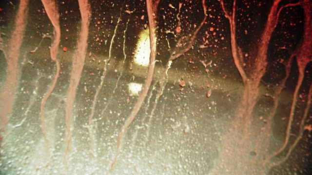 Soapy Water Streams Down a Vehicles Windshield before Being Rinsed with Clean Water in a Professional Car Wash