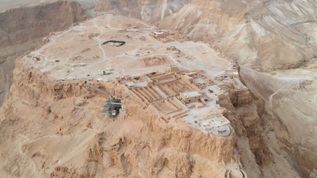 vista aerea impennata 4k masada, israele. drone volante filmato. che vola intorno a masada, un'antica fortezza ebraica nel deserto israeliano - archeologia video stock e b–roll