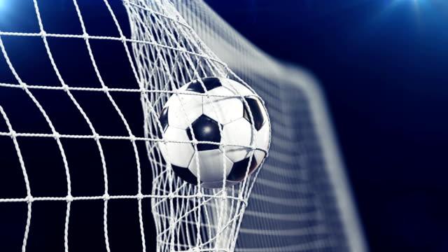 Fußball im Ziel Net in Zeitlupe fliegen. Schwarzen Hintergrund und Fackeln. Sport-Konzept. Schönen Fußball 3d Animation des Augenblicks Ziel. – Video
