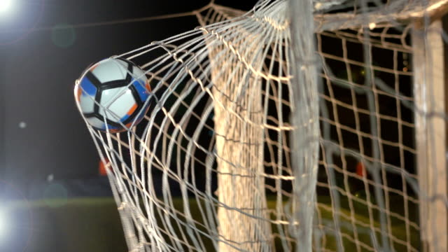 GOAL: Soccer ball / Football being scored in net - Super Slow Motion Stock HD video clip footage of a goal being scored in the net during a football match. There are floodlights on as the ball hits the back of the net in between the goalposts. Filmed in Super slow motion scoring a goal stock videos & royalty-free footage