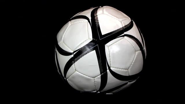 soccer ball is deflating on a black background, close up - platt bildbanksvideor och videomaterial från bakom kulisserna
