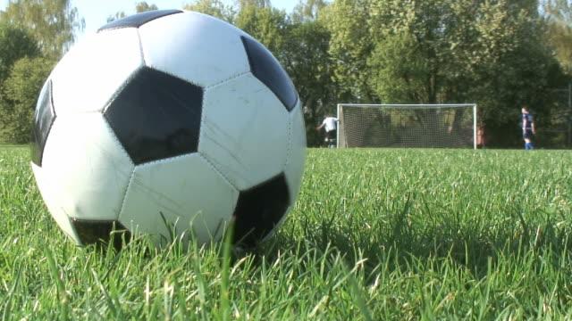 vídeos de stock, filmes e b-roll de bola de futebol em um campo de futebol, enquanto as pessoas desempenham - futebol internacional
