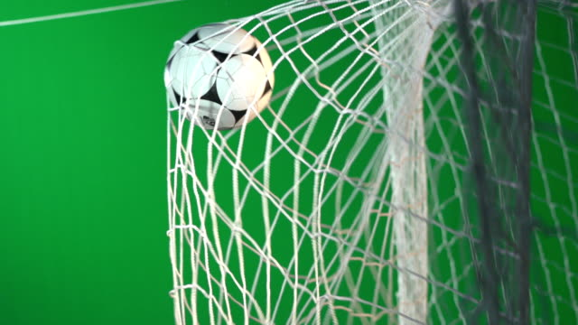 Soccer ball, Scoring football goal in net - Chroma key Green Screen - Super Slow Motion Stock HD video clip footage of a goal being scored in the net during a football match. There are floodlights on as the ball hits the back of the net in between the goalposts. Filmed in Super slow motion. FIlmed for keying Chromakey on a Green screen background. scoring a goal stock videos & royalty-free footage