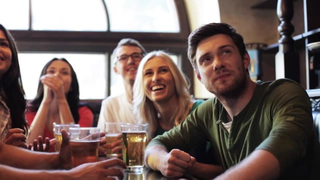 soccer fans watching football match at bar or pub people, leisure and sport concept - happy friends or football fans drinking beer and watching soccer game or match at bar or pub match sport stock videos & royalty-free footage