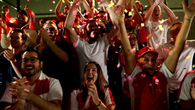 Soccer / Football fans in Stadium with confetti / Ticker tape - Super Slow Motion video