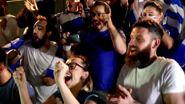 vídeos de stock e filmes b-roll de soccer / football supporters in stadium celebrating goal being scored - super slow motion - adeptos