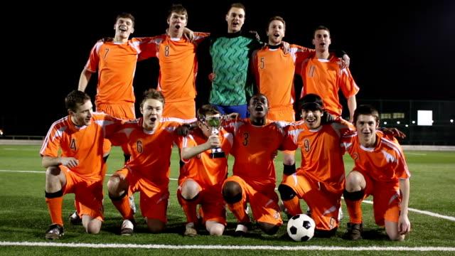 vídeos de stock e filmes b-roll de futebol/equipa de futebol celebram como partidários com troféu (vencedores - equipa desportiva