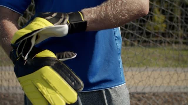 portiere di calcio che regola i guanti del portiere all'aperto - guanto indumento sportivo protettivo video stock e b–roll