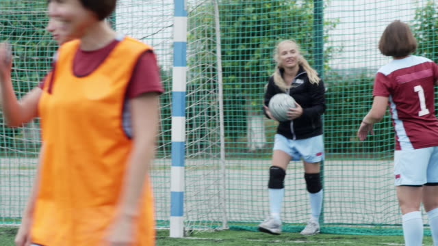 Soccer goalkeeper taking ball after game Female soccer goalkeeper discussing match with her teammate in time-out on outdoor playground goal post stock videos & royalty-free footage